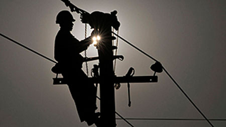 Техник работает над устранением сбоя в электростолбе